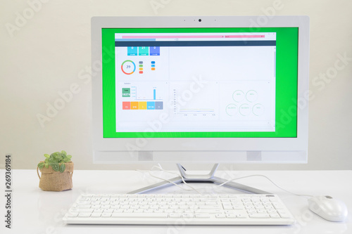 All in one PC on white table with statistics monitor