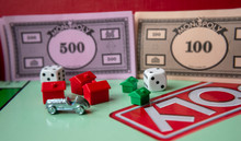 Monopoly Board Game, Playing Pieces, Cards, Dice On Red Background