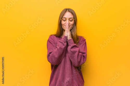 Young casual woman praying very happy and confident Canvas Print