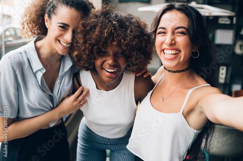 Foto  three young multiracial women having fun and looking camera