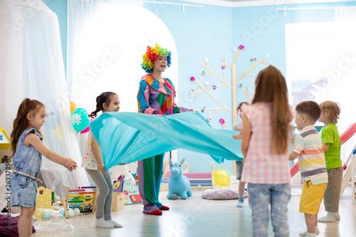 Fotografía Children group have fun on birthday party. Clown entertains kids