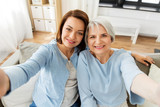 family, generation and people concept - portrait of senior mother and adult daughter taking selfie at home - 269382910