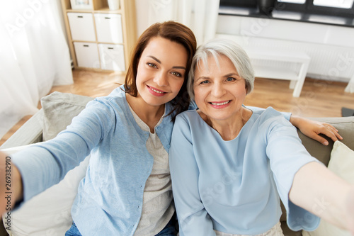 family, generation and people concept - portrait of senior mother and adult daughter taking selfie at home