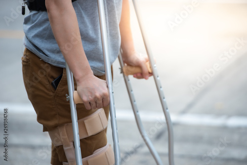 Papel de parede Disabled woman with crutches or walking stick or knee support standing in back side,half  body