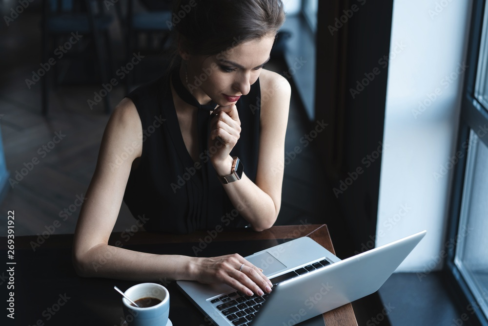 Fototapeta Concentrated at work. Confident young woman in smart casual wear working on laptop while sitting near window in creative office or cafe.