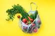 Leinwandbild Motiv Eco friendly mesh bag with organic green vegetables on yellow paper background. Flat lay, top view. Zero waste, plastic free concept. Healthy clean eating diet and detox.