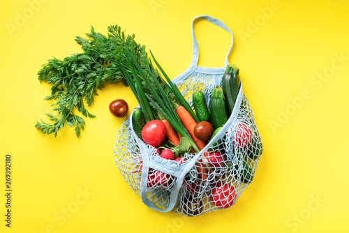Foto auf Leinwand Texturen Eco friendly mesh bag with organic green vegetables on yellow paper background. Flat lay, top view. Zero waste, plastic free concept. Healthy clean eating diet and detox.