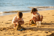Kids Making Sand Castle On The...