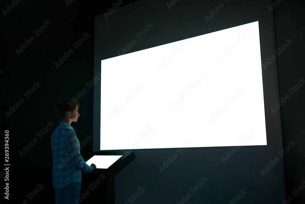 Obraz Woman using electronic kiosk and looking at white blank large interactive wall display in dark room of modern technology exhibition. Mock up, futuristic, template, education and technology concept fototapeta, plakat