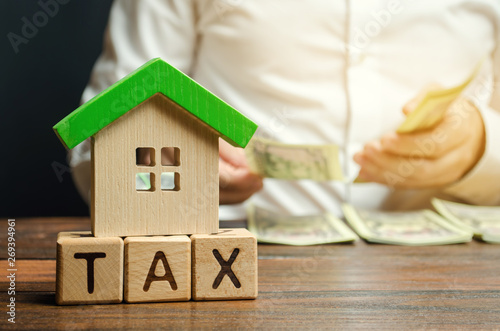 Fototapeta Wooden blocks with the word Tax, house with money in the hands of a businessman. The concept of paying tax for housing and property. Debt payment. Property taxes. Mortgage obraz