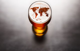 Fototapeta Uliczki - world map silhouette on foam in beer glass on black table. The continents shapes are altered ones from visibleearth.nasa.gov