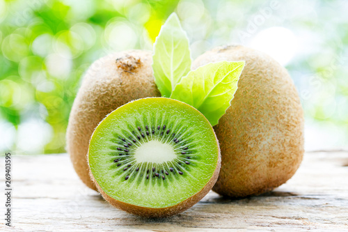 Fotografia kiwi fruits that are cut on a wooden floor with a natural backdrop