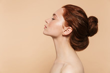 Young Redhead Woman Posing Isolated Over Beige Wall Background.
