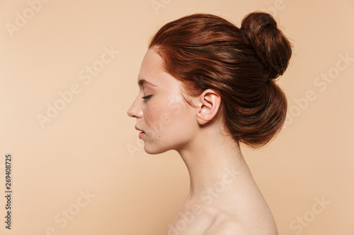 Fotografía  Young redhead woman posing isolated over beige wall background.
