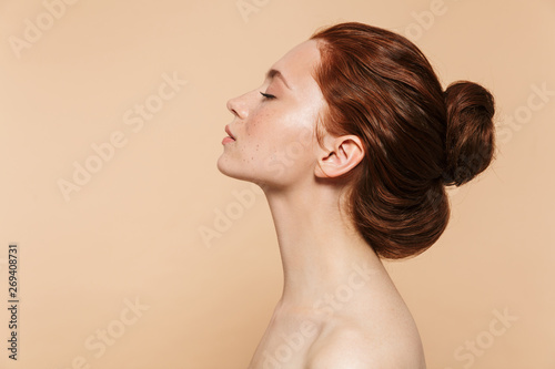 Carta da parati  Young redhead woman posing isolated over beige wall background.