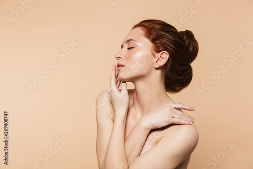 Fotomural  Amazing young redhead woman posing isolated over beige wall background