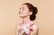 Pretty young redhead woman posing isolated over beige wall background pink flower.