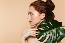 Pretty Young Redhead Woman Posing Isolated Over Beige Wall Background With Leaf Green Flowers.