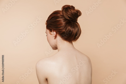 Obraz na plátně Back view photo of a young redhead woman