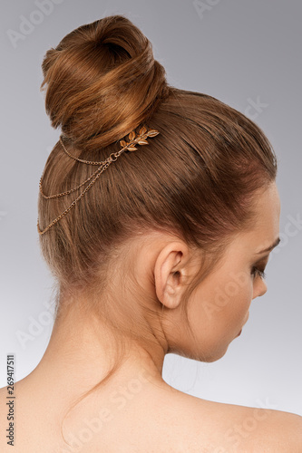 Cropped Back View Closeup Shot Of Lady With Massive Bun Adorned With Golden Hairpin With Long