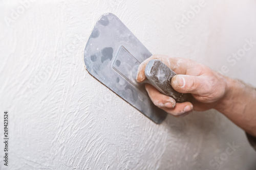 Man is priming a surface with a sandpaper. Grind of wall. Maintenance repair works renovation in the flat. Restoration indoors. Concrete background.