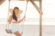 Asian young woman wearing white dress smile enjoy on swing with summer vacation on pier on beach feeling so happiness and cheerful,Travel in tropical beach in Thailand,vacations and relaxation Concept