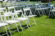 Rows Of White Folding Chairs On Lawn Before A Wedding Ceremony In Summer