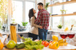 Image of romantic couple at home. Attractive young woman and handsome man are enjoying spending time together while standing on light modern kitchen, drinking wine.