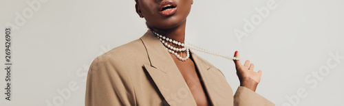 cropped view of seductive african american woman in beige jacket and necklace is Fotobehang
