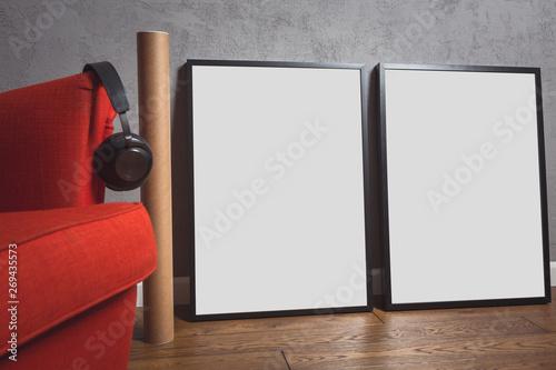 Obraz Pusta ramka na plakat stoi na drewnianej podłodze i opiera się o betonową ścianę. Obok stoi czerwony fotel, na którym wiszą słuchawki muzyczne. - fototapety do salonu