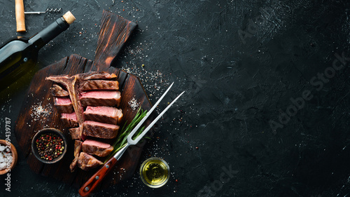 Fotobehang Steakhouse Beef T-Bone steak on a black table. Top view. Free space for text.