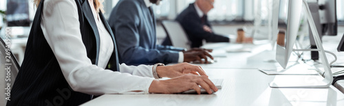Obraz panoramic shot of businesswoman working near multicultural coworkers - fototapety do salonu