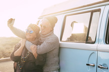 Travel And Alternative People Vacation Concept For Senior Retired Lifestyle Couple Taking Selfie Picture For Social Media - Vintage Van In Background - Sunset Sunlight And Forever Concept