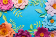 Leinwandbild Motiv top view of multicolored paper cut flowers with leaves on blue background with copy space