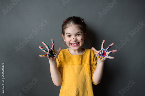 Fotografie, Obraz  Happy little girl with colored hands on a gray background, young artist