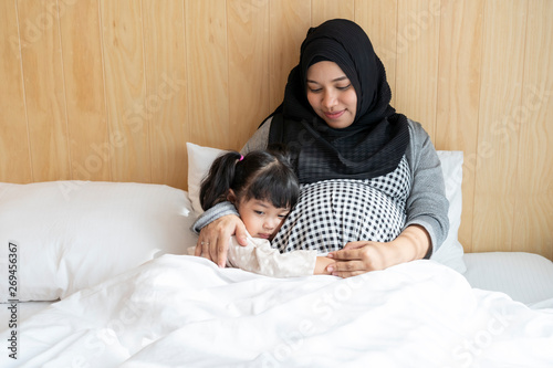 Asian Muslim Indonesian pregnant woman and her daughter