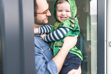 Father Carrying Smiling Son In Costume At Doorway