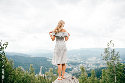 Foto auf Gartenposter Weiß Young beautiful barefoot blonde girl with long hair in summer dress standing on top of conquered mountain at stone and enjoying fabulous landscape scenic view with mountains and village in valley