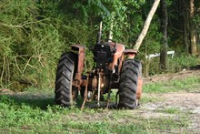 An Old Massey Ferguson Tractor Sits Abandoned With A Flat Tire At The Edge Of A Field On A Southern Farm.