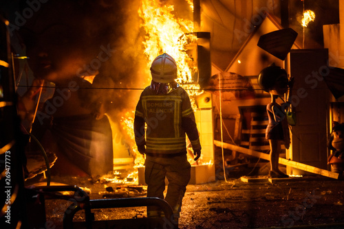 Firemen around a bonfire caused by a Falla Valenciana controlling the flames of the fire.