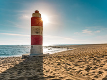 Beautiful Beach Scene With Old Red And White Lighthouse And Lens Flare From The Sun