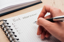 Cropped View Of Recruiter Writing In Notebook With Exit Interview Lettering