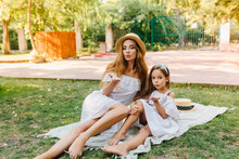 Barefooted Young Woman And Little Girl In Similar Dresses Sending Air Kisses While Lying On White Blanket In Park. Outdoor Portrait Of Lovely Mother And Daughter Chilling On Nature Background.