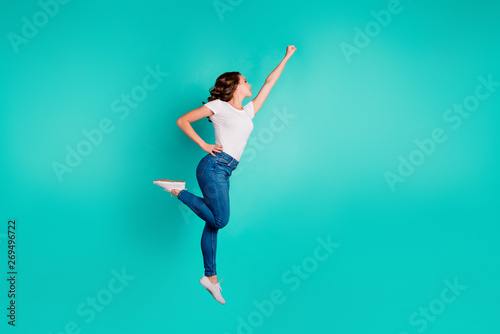 Obraz Full length body size profile side view of her she nice-looking attractive cheerful slim fit thin slender wavy-haired lady raising hand up aim isolated on bright vivid shine blue background - fototapety do salonu