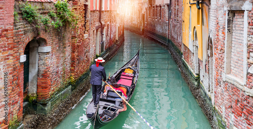 Foto Venetian gondolier punting gondola through green canal waters of Venice Italy