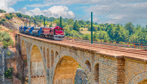 Photo Red passenger diesel train moving at the bridge - Varda railway bridge, Adana Tu