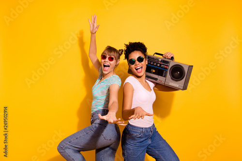 Portrait of beautiful positive cheerful content student enjoy active journey holiday beach hold hand sing wavy curly top-knot trendy style stylish t-shirt jeans specs funky isolated yellow background - 269502914
