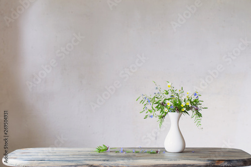Wall Murals Floral wildflowers in white vase on background old wall