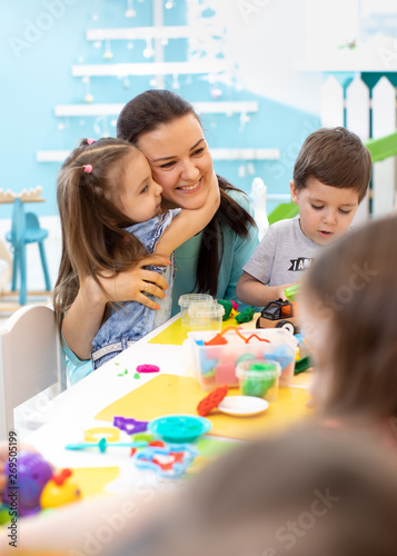 Teacher with group of kids working with plasticine at kindergarten or playschool