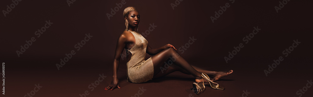 Fototapeta seductive african american woman with short hair posing in glamorous dress on brown